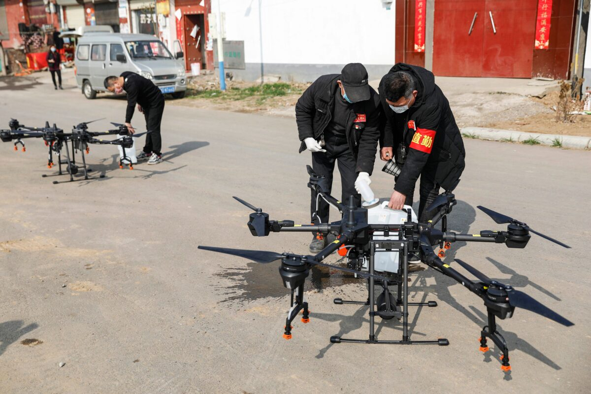 Local residents fills a drone with disinfectant