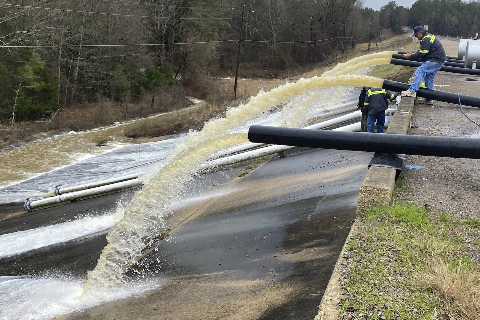Crews work to replace drainage pipes at the Oktibbeha County Lake dam in Starkville, Miss.