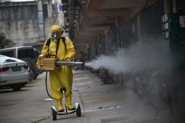 A medical staff member sprays disinfectant