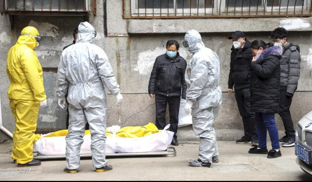 Funeral home workers remove the body