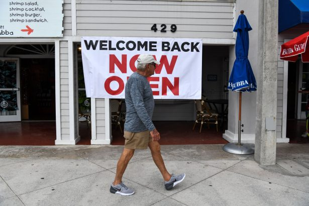 """A man walks past a sign reading """"Welcome Back, Now Open"""""""