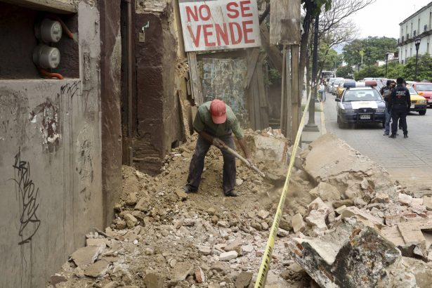 A man removes rubble from a building damaged by an earthquake in Oaxaca Mexico