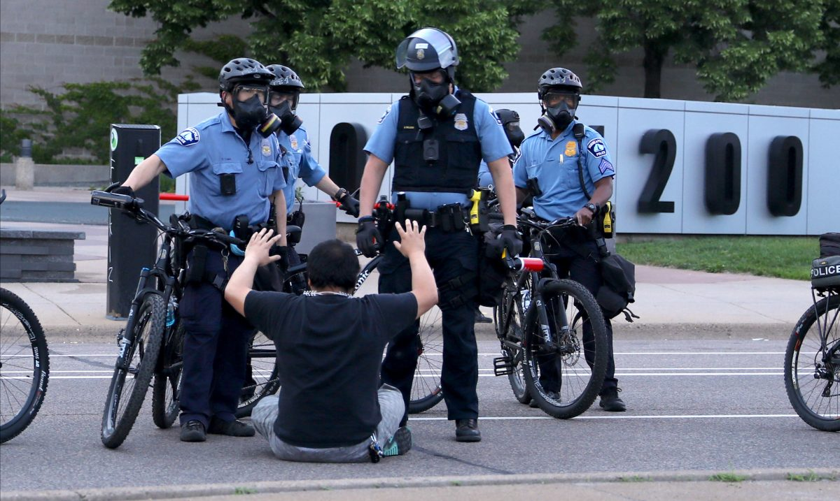 A protester is detained by police