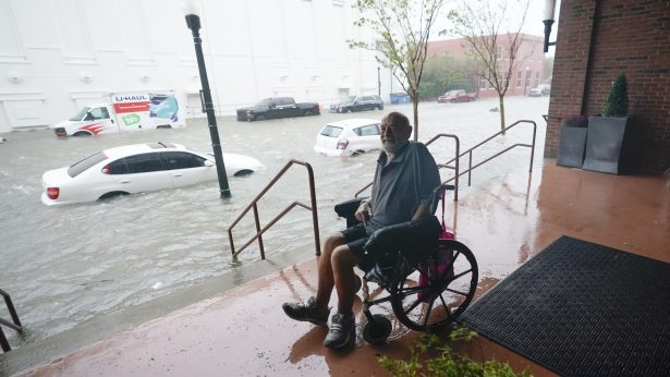 A man watches floodwaters