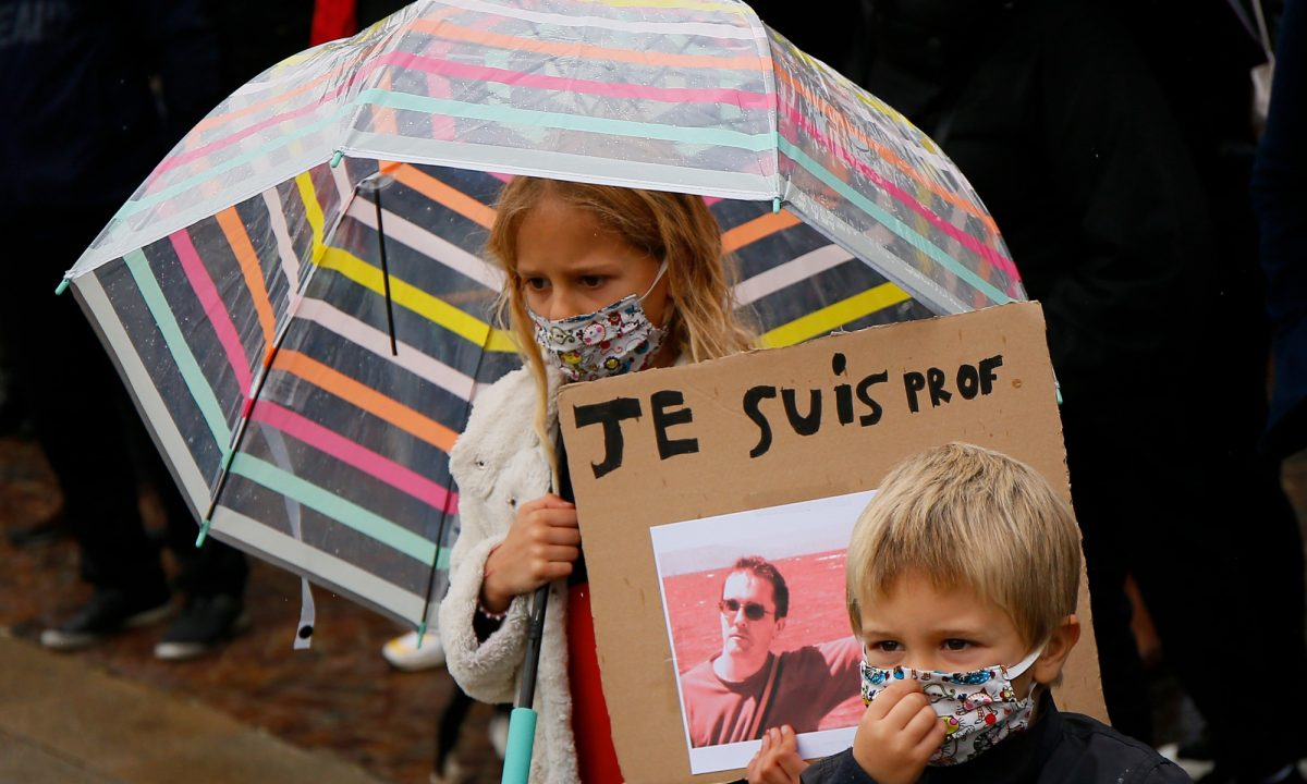 A child holds up a a poster of Samuel Paty