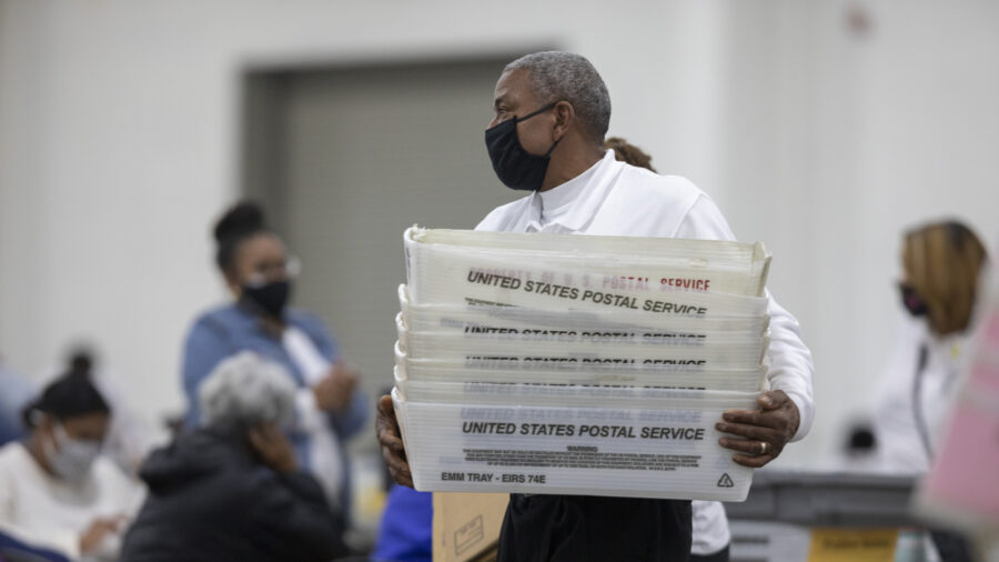A worker with the Detroit Department of Elections carries empty boxes used to organize absentee ballots after nearing the end of the absentee ballot count at the Central Counting Board in the TCF Center in Detroit, Mich. on Nov. 4, 2020. (Elaine Cromie/Getty Images)