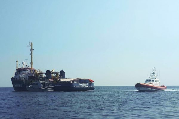 An Italian Coast Guard boat patrols next to the Sea-Watch 3 vessel