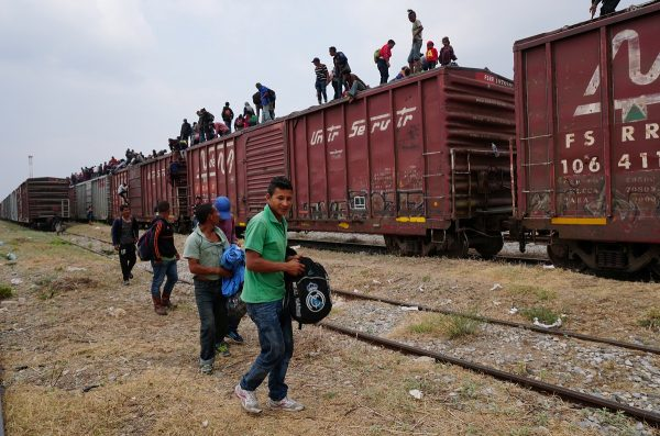 Central American migrants ride atop train