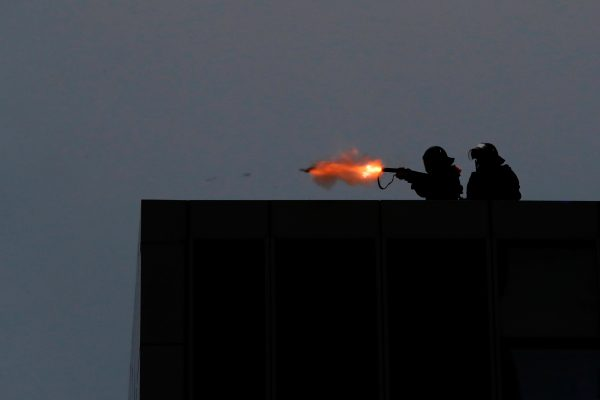 Riot police fires tear gas from the balcony of the government headquarters building to disperse protesters.