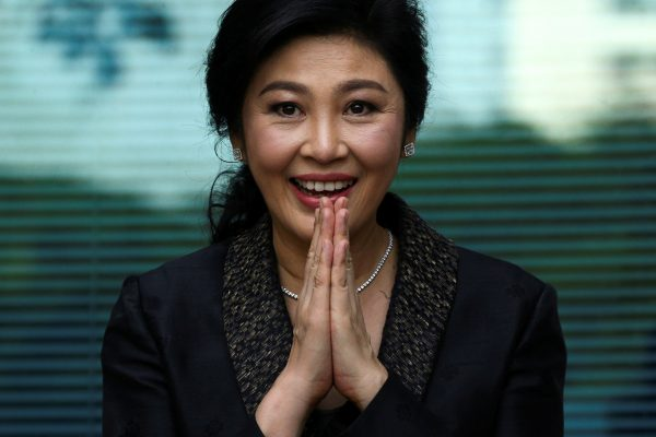 Thai prime minister Yingluck Shinawatra greets supporters as she arrives at the Supreme Court in Bangkok