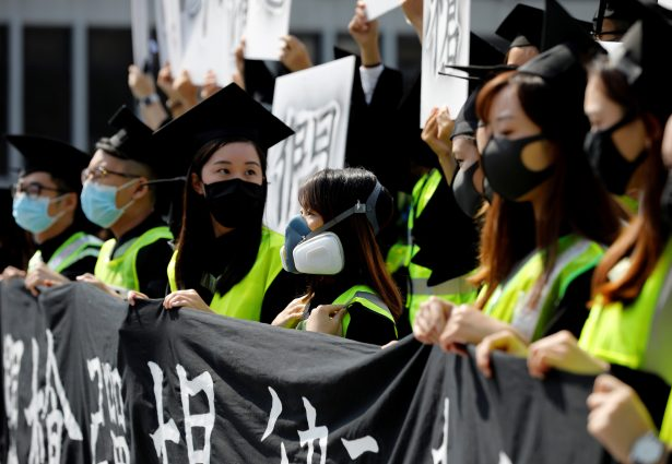 Graduates wearing masks hold an anti-government rally after their graduation ceremony at the Chinese University of Hong Kong in Hong Kong