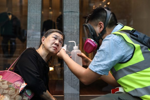 A woman is treated after police fired tear