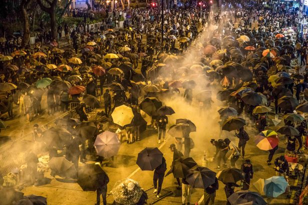 Protesters react as police fire tear gas