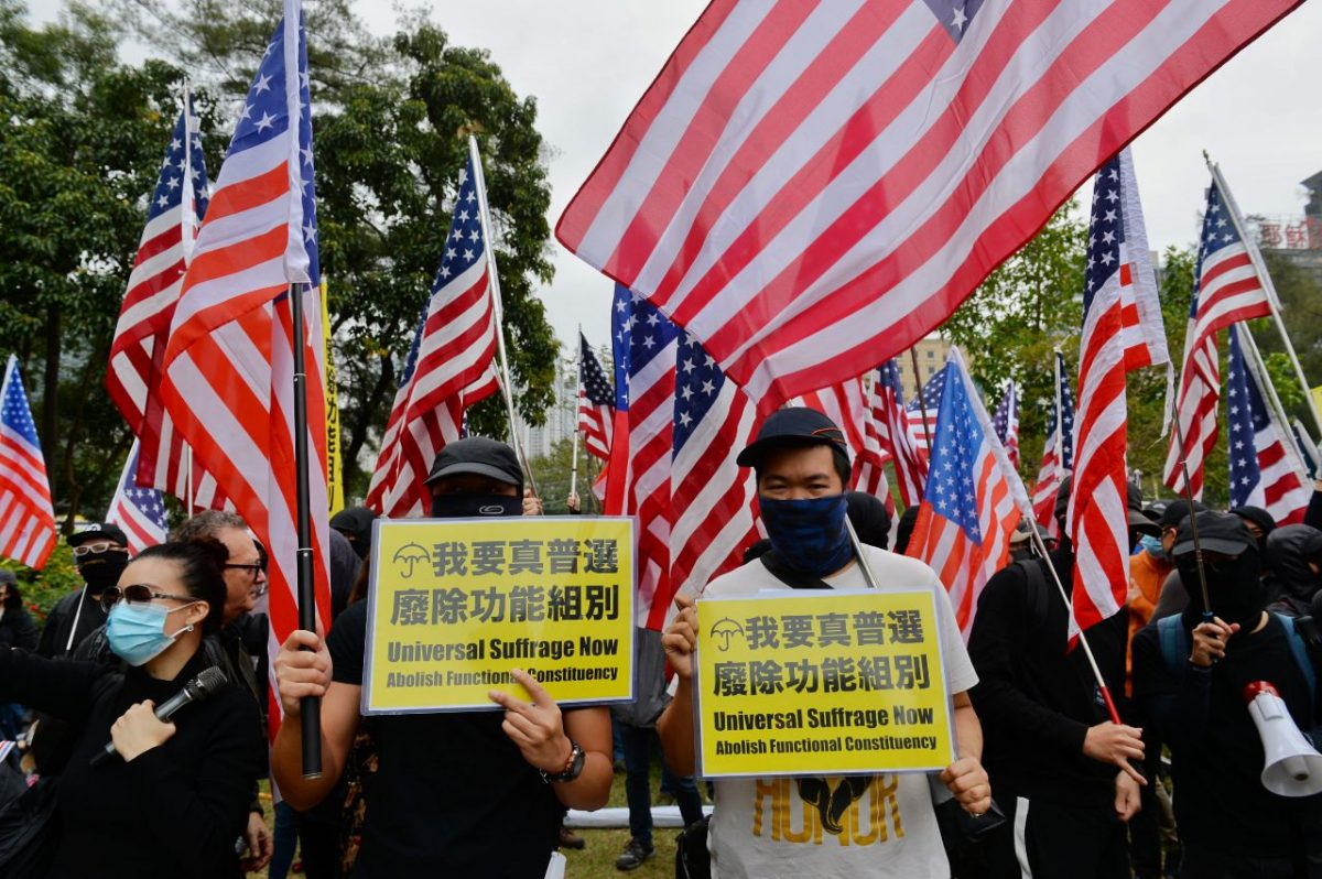 Two protesters hold up placards demanding universal suffrage