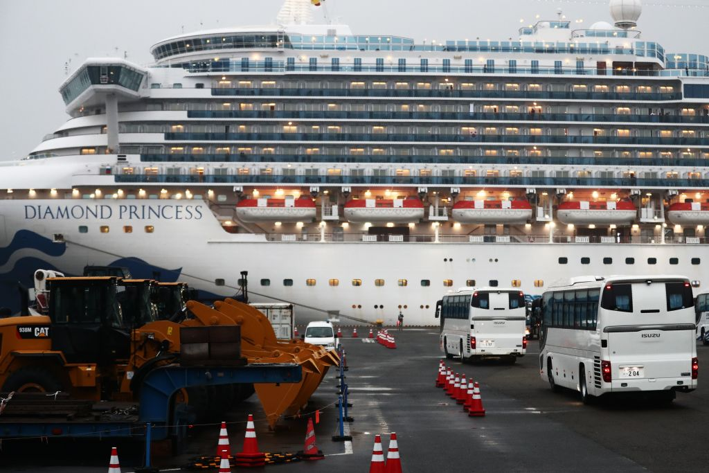 Two buses arrive next to the Diamond Princess cruise ship