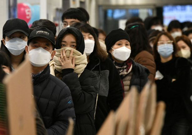 People wait in line to buy face masks