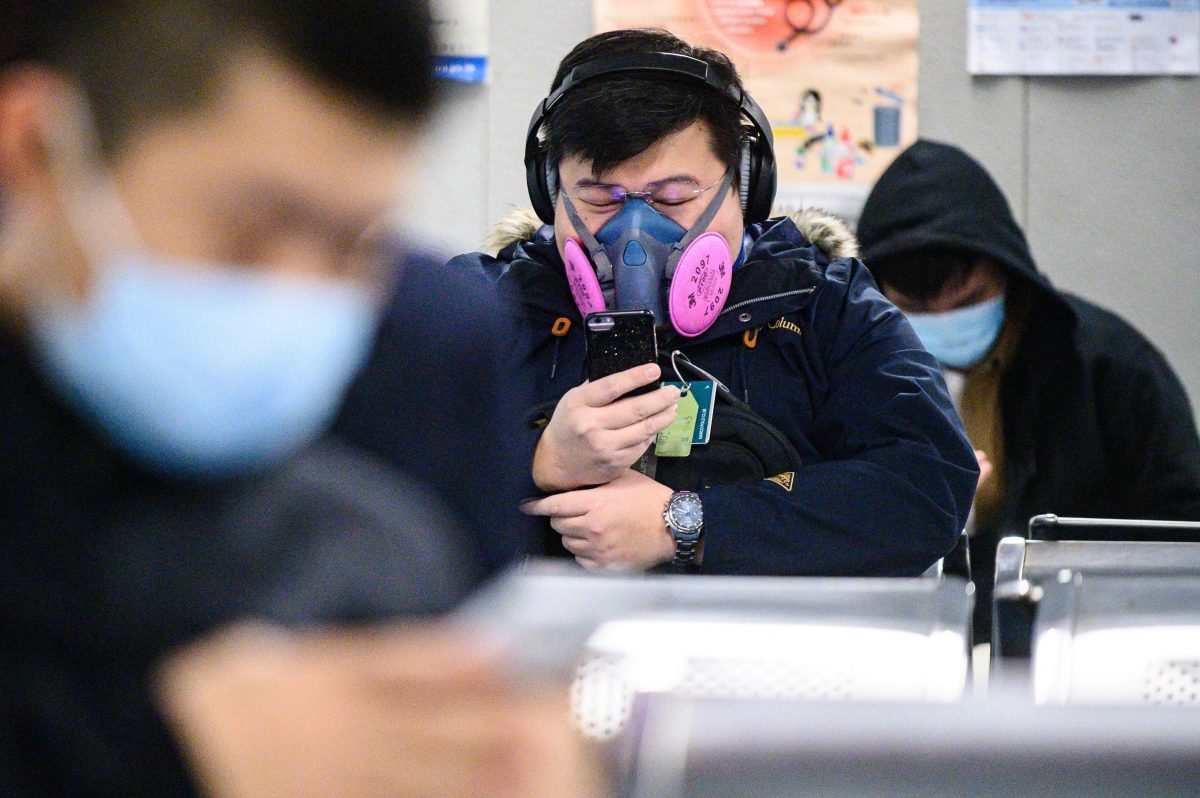 A man wearing a respirator mask waits for his ferry