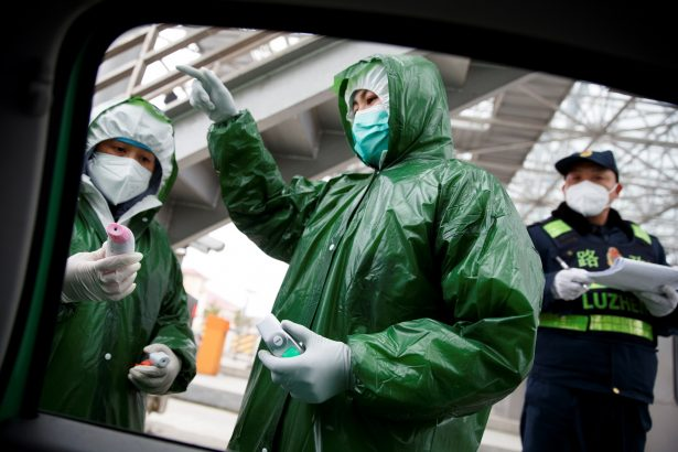 Medical and security workers stand at a checkpoint to screen for the new coronavirus