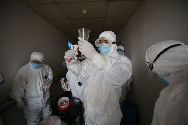 Workers prepare to disinfect rooms a