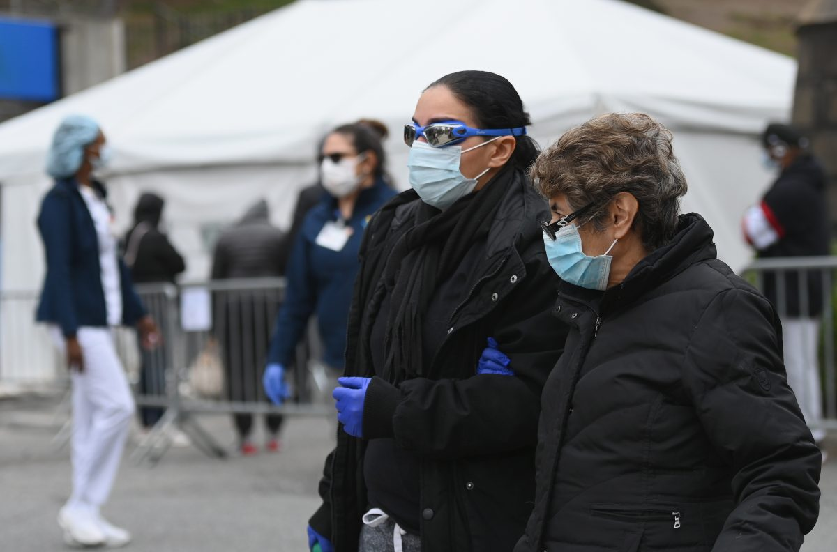 People wearing masks and goggles pass