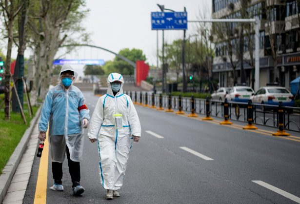 Two people, wearing protective suits