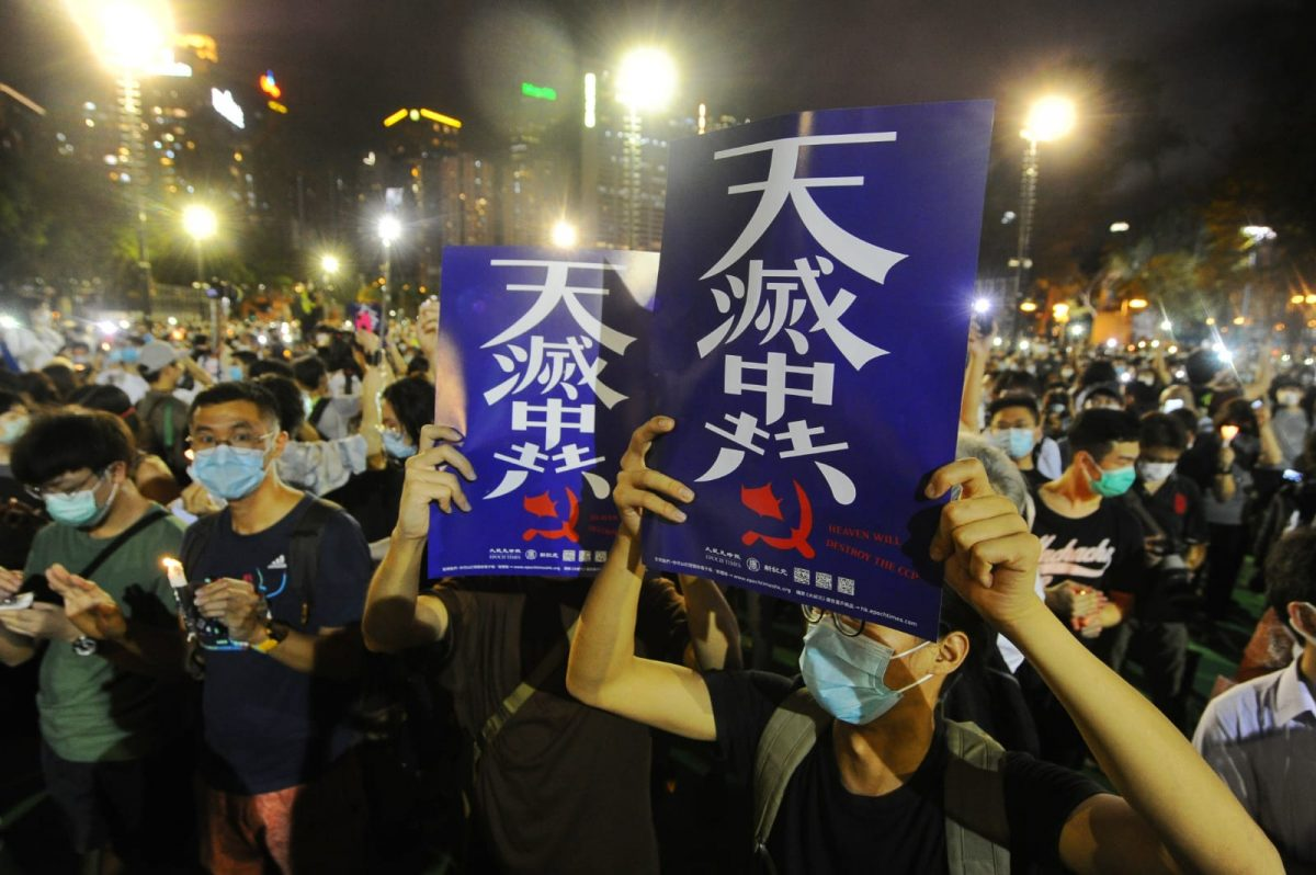 """People hold up placards with the words """"The Heavens Will Destroy the Chinese Communist Party"""""""