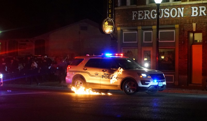 A Molotov cocktail hits a police car
