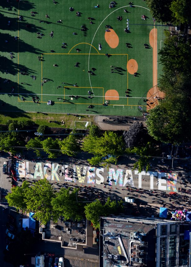 "Artists fill in the letters of a ""Black Lives Matter"" mural"