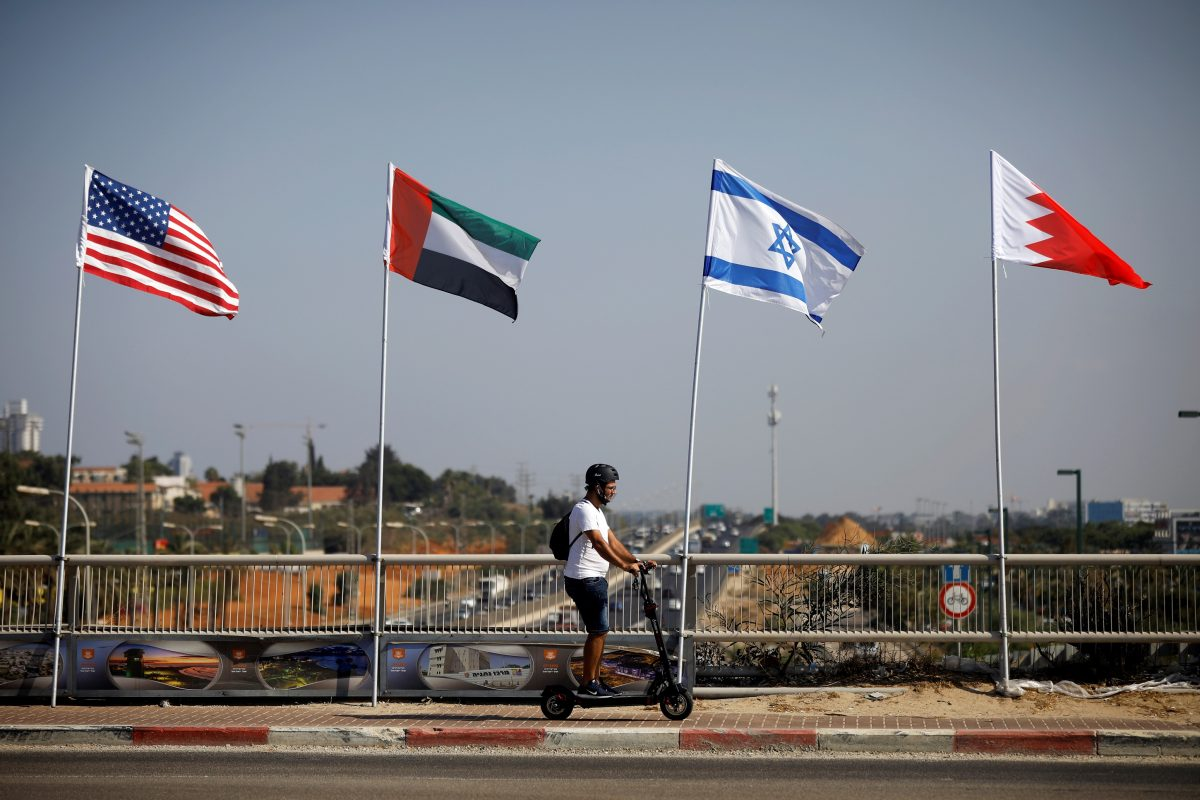 A man rides a scooter near the flags
