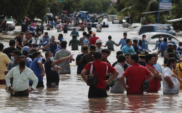 Residents wade through a flooded road